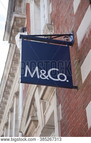 The M & Co Sign Hanging On A Wall Above A Shop In The Uk, Taken On The 20th July 2020
