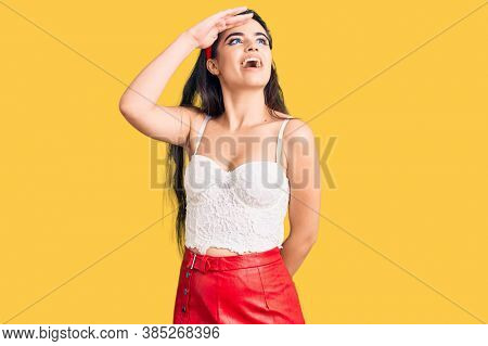 Brunette teenager girl wearing elegant look very happy and smiling looking far away with hand over head. searching concept.