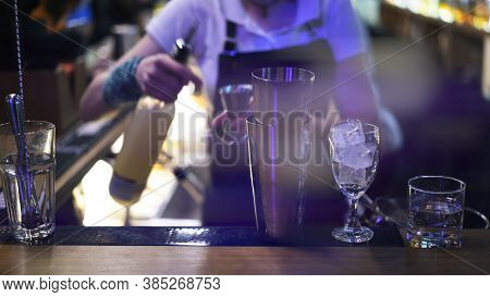 Metal Cups And Glasses On Bar Counter On Background Of Bartender Pouring Alcohol, Lens Flare. Bar Co