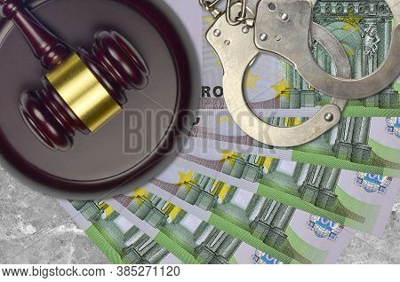 100 Euro Bills And Judge Hammer With Police Handcuffs On Court Desk. Concept Of Judicial Trial Or Br