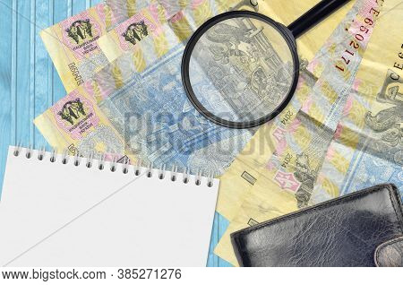 1 Ukrainian Hryvnia Bills And Magnifying Glass With Black Purse And Notepad. Concept Of Counterfeit