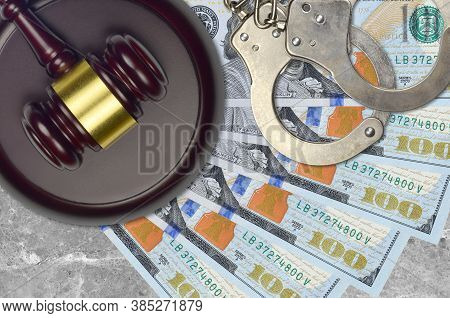 100 Us Dollars Bills And Judge Hammer With Police Handcuffs On Court Desk. Concept Of Judicial Trial