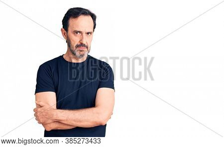 Middle age handsome man wearing casual t-shirt skeptic and nervous, disapproving expression on face with crossed arms. negative person.