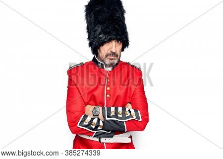 Middle age handsome wales guard man wearing traditional uniform over white background skeptic and nervous, disapproving expression on face with crossed arms. Negative person.