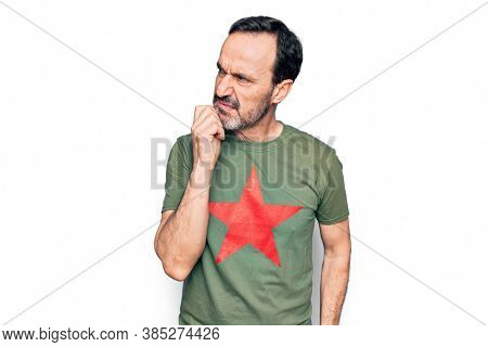 Middle age handsome man wearing t-shirt with revolutionary red star over white background thinking concentrated about doubt with finger on chin and looking up wondering