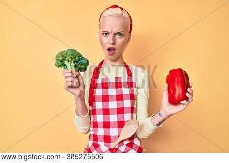 Young blonde woman with tattoo wearing cook apron holding broccoli and red pepper in shock face, looking skeptical and sarcastic, surprised with open mouth
