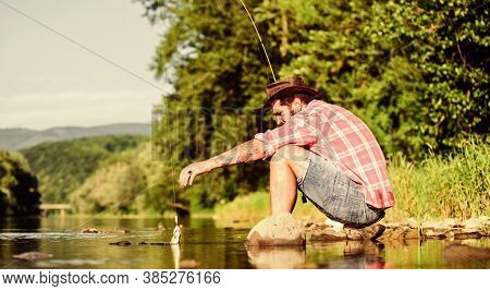Gone Fishing. Successful Fisherman In Lake Water. Hipster Fishing With Spoon-bait. Big Game Fishing.