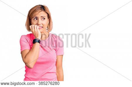 Young blonde woman wearing sportswear looking stressed and nervous with hands on mouth biting nails. anxiety problem.