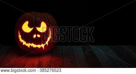 carved halloween pumpkin with candle inside on wooden planks.