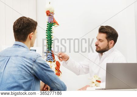 Doctor Showing Flexible Spine Model To His Patient And Explains The Cause Of His Pain In Medical Off