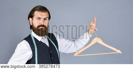 Formal Stylish Mens Clothing On Hanger Stand In Room. Tailor Man Holds In His Hand A Hanger. Handsom