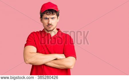 Young handsome man with curly hair wearing delivery uniform skeptic and nervous, disapproving expression on face with crossed arms. negative person.