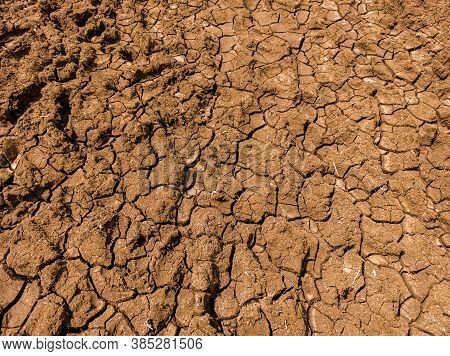 Dry Black Cotton Soil In Summer Season. Broken Soil, Dry Soil Pattern Texture.