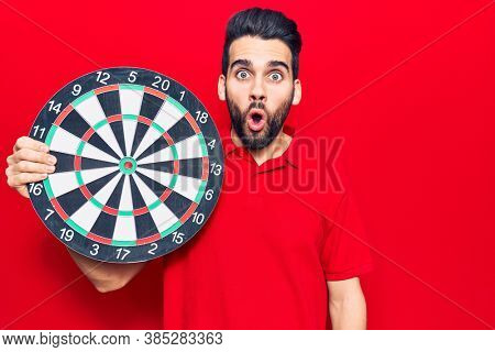 Young handsome man with beard holding dartboard scared and amazed with open mouth for surprise, disbelief face