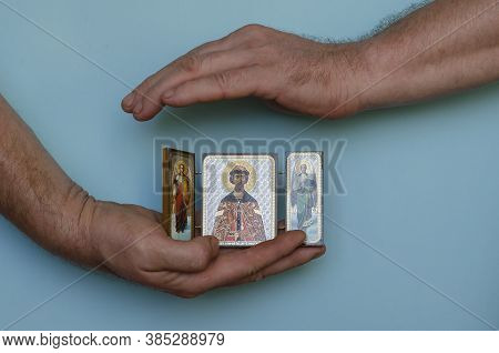 Hands Hold The Christian Icon Of Dmitry Donskoy And The Archangels Gabriel And Michael. Male Hands W