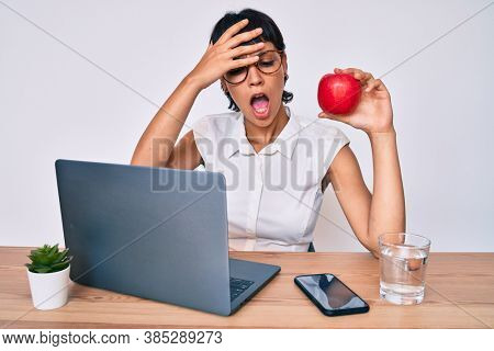 Beautiful brunettte woman working at the office eating healthy apple stressed and frustrated with hand on head, surprised and angry face
