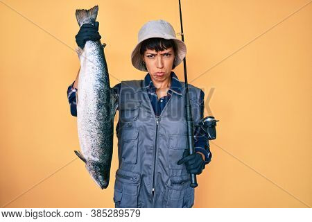 Beautiful brunettte fisher woman holding fishing rod and raw salmon depressed and worry for distress, crying angry and afraid. sad expression.