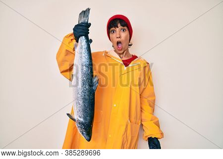 Beautiful brunettte fisher woman wearing raincoat holding fresh salmon scared and amazed with open mouth for surprise, disbelief face