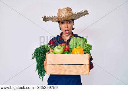 Beautiful brunettte woman wearing farmer clothes holding vegetables in shock face, looking skeptical and sarcastic, surprised with open mouth