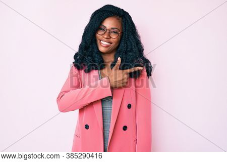 Beautiful african woman wearing business jacket and glasses cheerful with a smile of face pointing with hand and finger up to the side with happy and natural expression on face