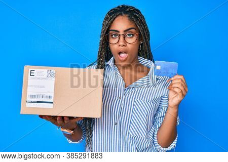 Young african american woman with braids holding delivery box and credit card in shock face, looking skeptical and sarcastic, surprised with open mouth