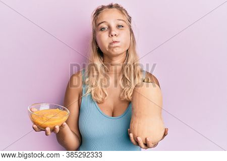 Young blonde woman holding fresh pumpkin and soup puffing cheeks with funny face. mouth inflated with air, catching air.