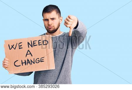 Young handsome man holding we need a change banner with angry face, negative sign showing dislike with thumbs down, rejection concept
