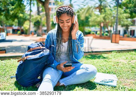 Young african american student woman smiling happy listening to music sitting on the grass at the university campus