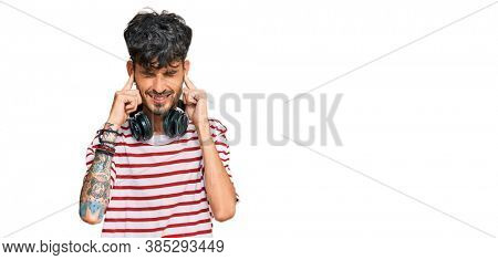 Young hispanic man listening to music using headphones covering ears with fingers with annoyed expression for the noise of loud music. deaf concept.