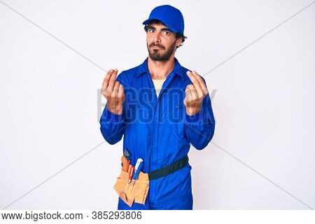 Handsome young man with curly hair and bear weaing handyman uniform doing money gesture with hands, asking for salary payment, millionaire business
