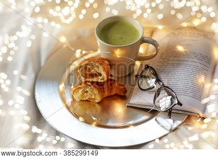 morning, hygge and breakfast concept - croissants, cup of matcha tea book and glasses in bed at home