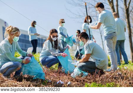 volunteering, charity and ecology concept - group of volunteers wearing face protective medical mask for protection from virus disease with garbage bags cleaning outdoor area