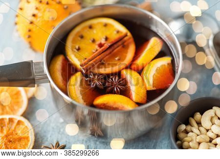 christmas and seasonal drinks concept - pot with hot mulled wine, orange slices and aromatic spices on grey background