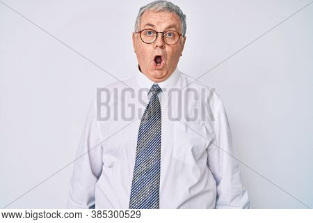 Senior grey-haired man wearing business clothes scared and amazed with open mouth for surprise, disbelief face