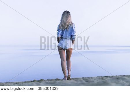 A Young Beautiful Sexy Woman Stands On The Lake And Looks Into Distance At Horizon In Evening. Rear