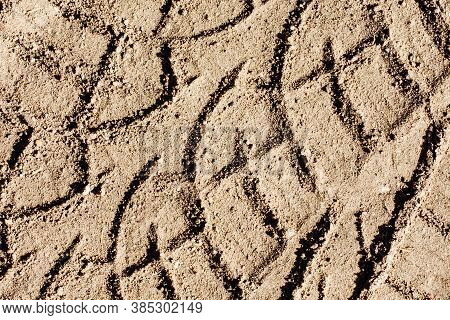 Tyre Mark Background. Tire Track Shape. Trail Lines On Dry Yellow Sand Pattern.