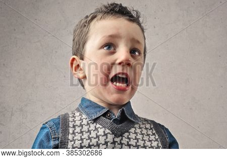 portrait of frightened child on the grey background