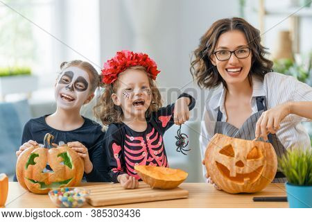 Happy family preparing for Halloween. Mother and children in carnival costumes at home.