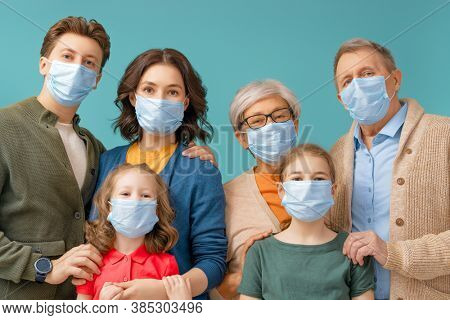 Family is wearing facemasks during coronavirus and flu outbreak. Virus and illness protection, quarantine. COVID-2019. Taking on masks. People on blue wall background.