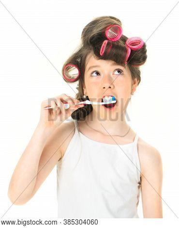 Teen In Hair Curlers. Little Girl On Morning, Brushing Teeth. Small Lady In Pyjamas. Teenager Brushi