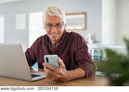 Mature man using smartphone in living room. Happy senior businessman working at home while messaging on mobile phone. Happy smiling old man using social media network technology and feeling excited.