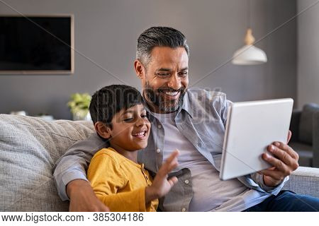 Indian father and smiling son sitting on couch using digital tablet at home. Man and boy using tablet for video calling at home. Middle eastern dad with son doing videocall during quarantine.