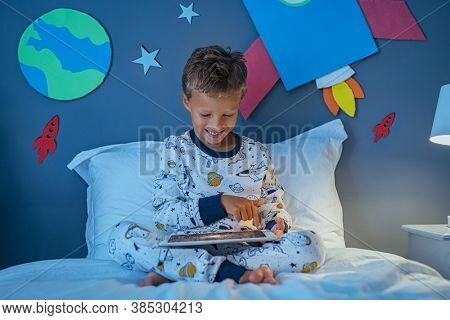 Boy using digital tablet to search images about solar system and outer space. Excited child in bedroom decorated with planets and rocket using digital tablet to learn about astronomy and cosmonaut.