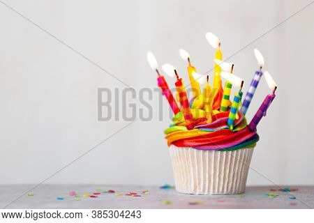 Birthday cupcake with rainbow frosting and colorful birthday candles