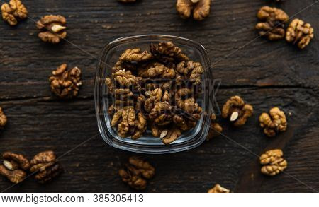 Walnut In A Smale Plate With Scattered Shelled Nuts And Whole Nut Which Standing On A Wooden Vintage