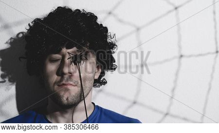 Portrait Of An Adult Man In A Black Wig With A Shadow Of A Spider And Cobwebs On His Face. Creates C