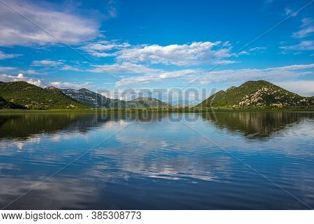 Beautiful Scenery Of Skadar (shkoder) Lake With Reflection Of Mountains And Clouds In The Water. Mon