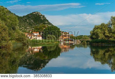 River Landscape Dodosi Town With Reflection  Mountains In The River. Skadar (shkoder) Lake, Monteneg