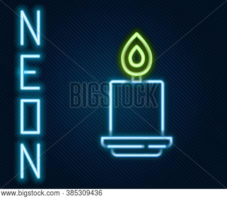 Glowing Neon Line Burning Candle Icon Isolated On Black Background. Cylindrical Aromatic Candle Stic