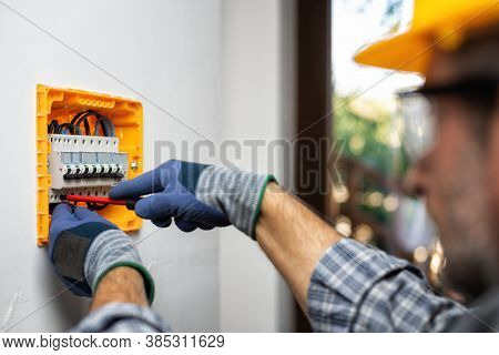 Electrician At Work With Screwdriver Fixes The Cable In The Switches Of An Electrical Panel In A Res